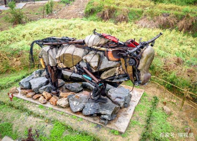 挖掘机废旧零件和石头制成田牛村口迎宾,栩栩如生,明显是个公牛