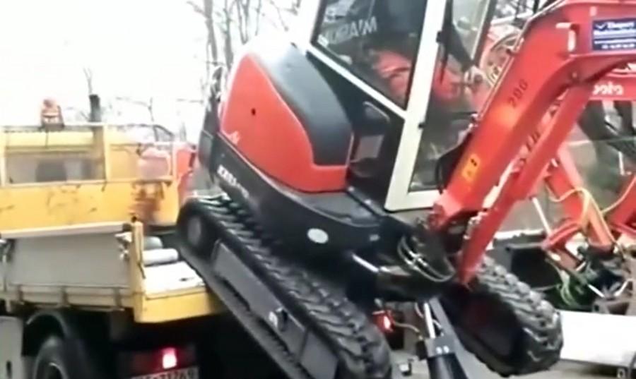 小型挖掘機上拖車,司機開到一半,還要下來看一下