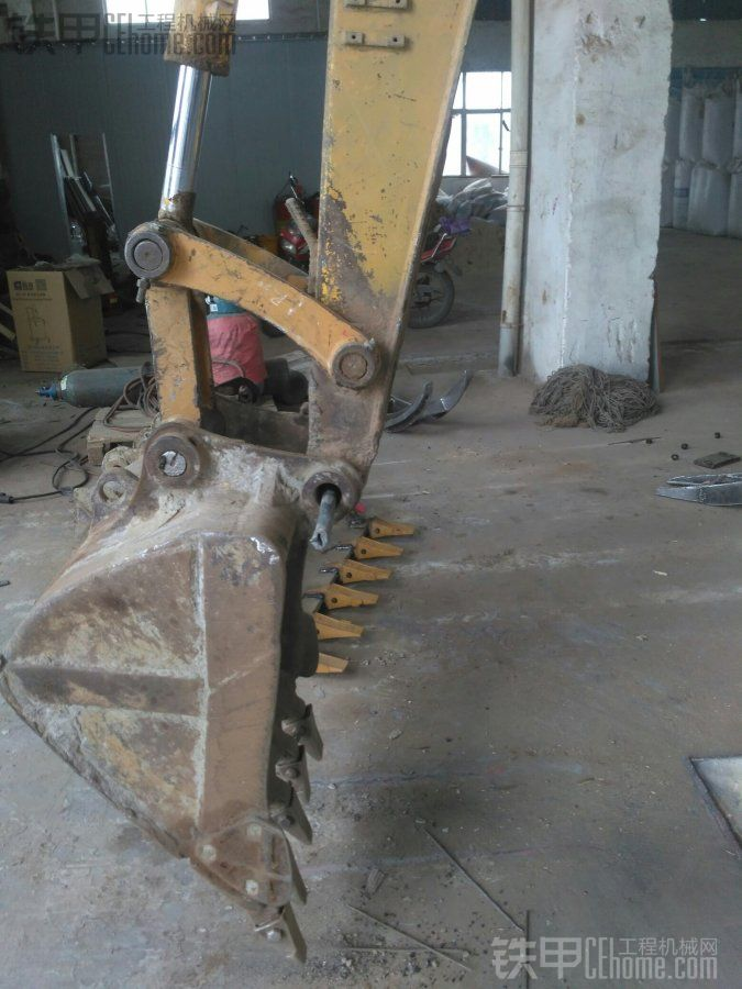 然后小臂往回收同时铲斗油缸一并往回收开始穿马头与斗耳的轴。