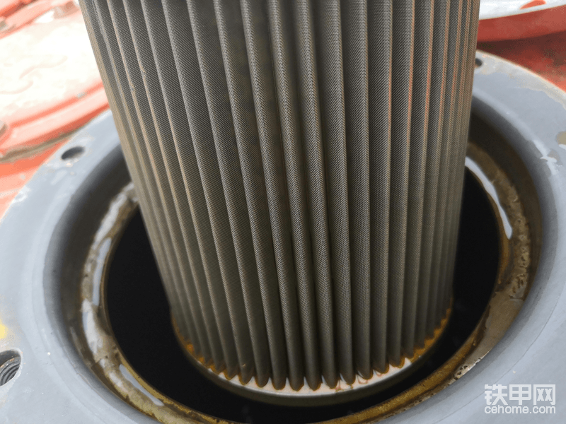 然后开始拿吸油滤芯开刀,打开这个液压油油箱盖之前一定确保油箱内部压力已经提前释放,不然可能会发生危险,日立60是个按阀,按下去以后就可以释放内部气压。另外在拆开盖子之前把周围的灰尘擦去,免得有风把灰尘吹进油箱里面。吸油滤芯是可以反复使用的,用干净的柴油清洗下就可以了,当我打开以后发现并没有杂质,索性就放弃清洗了😃